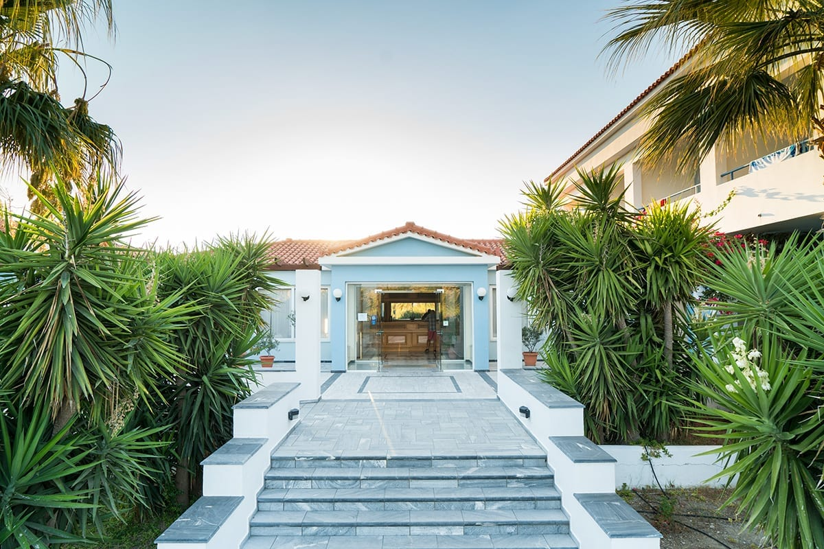 Steps up to the Zefiros Beach Hotel in Samos, surrounded by beautiful palm trees