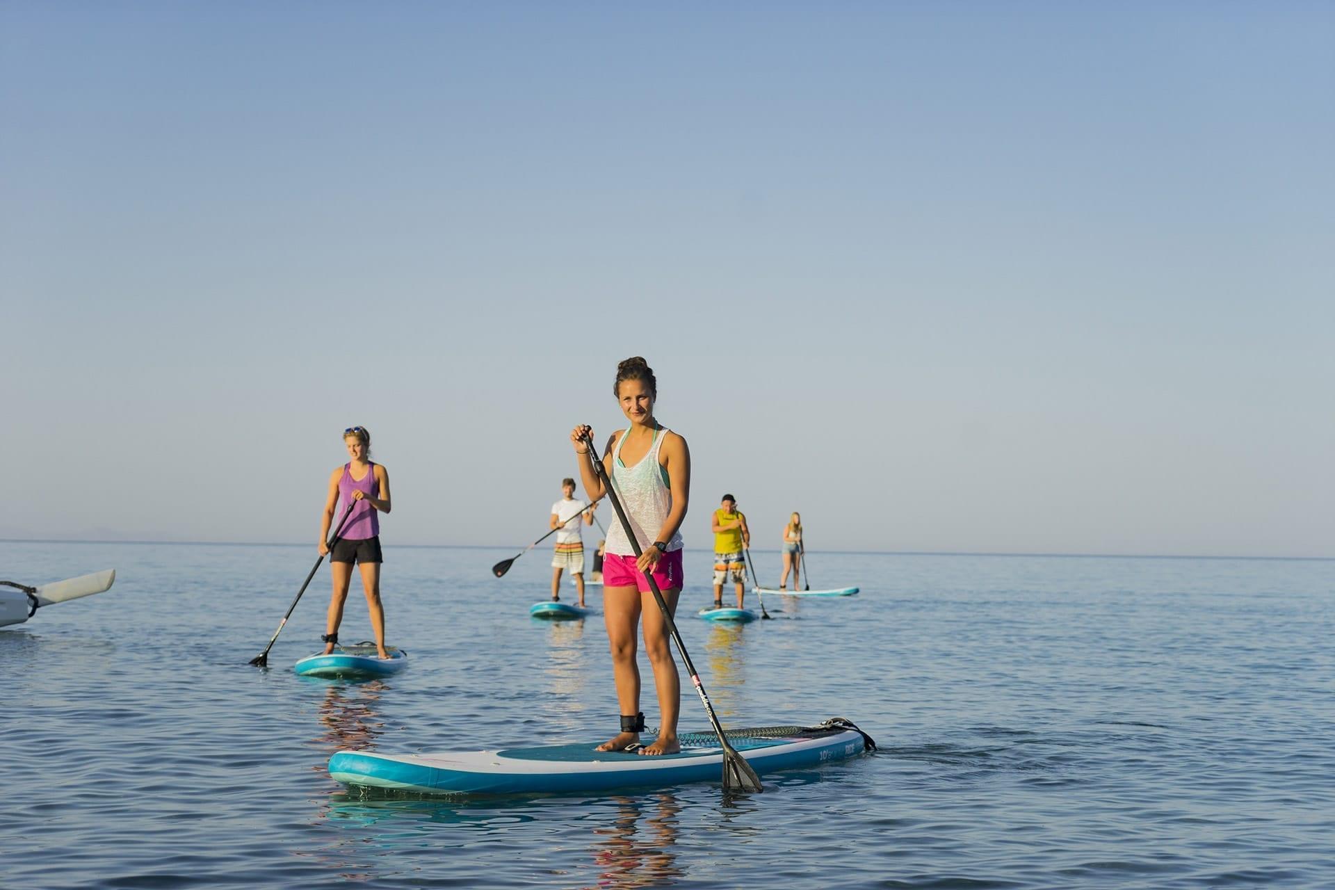 A group of friends paddle boarding in Mykali Bay, Samos, Greece