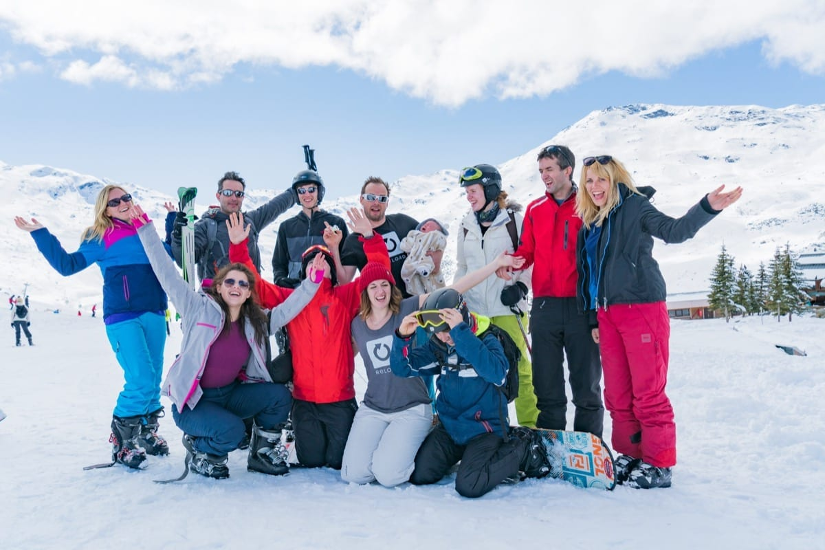 A group of guests with Richmond Christian holidays smiling in the snow and holding their ski equipment