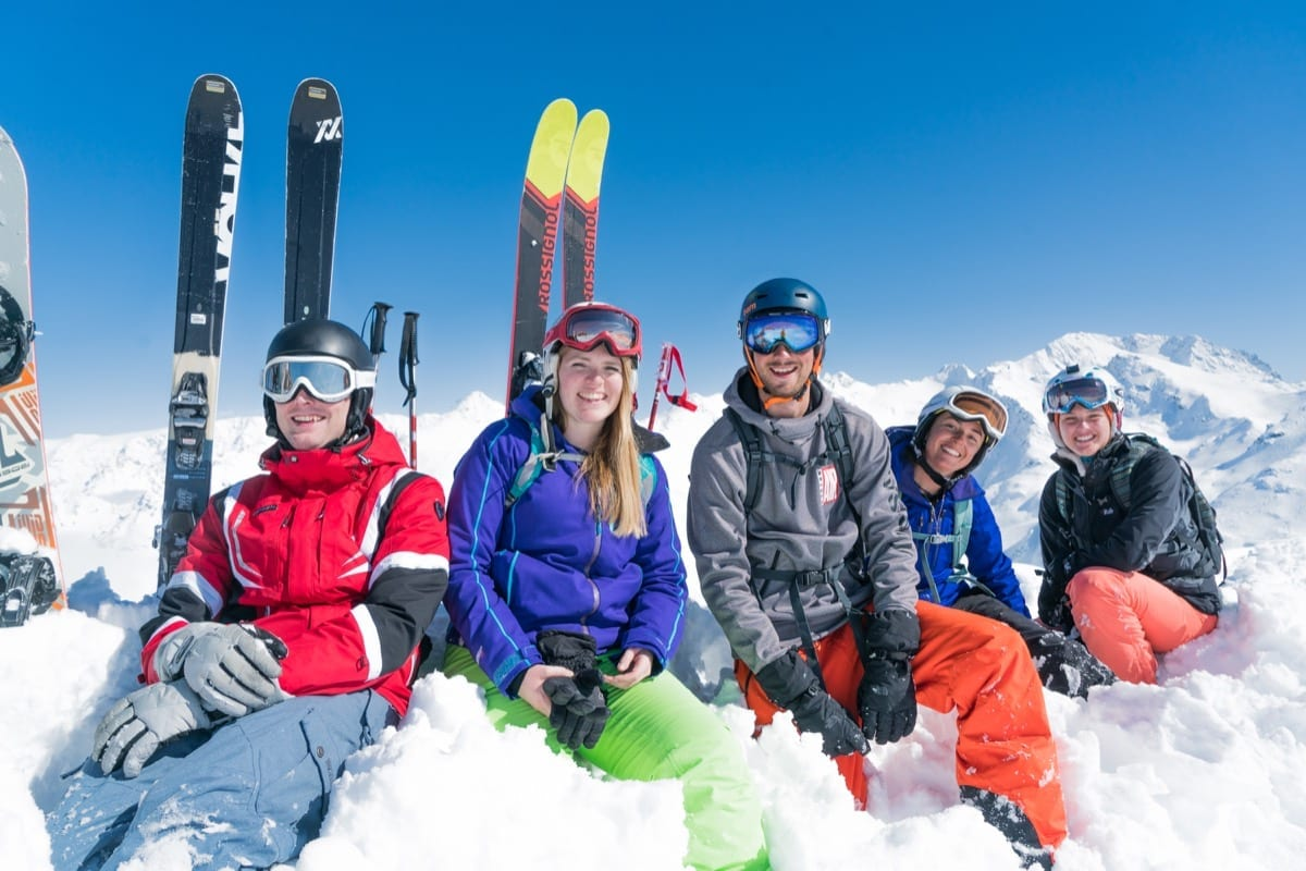 A group of friends smiling as they take a break with their skis, sitting in snow