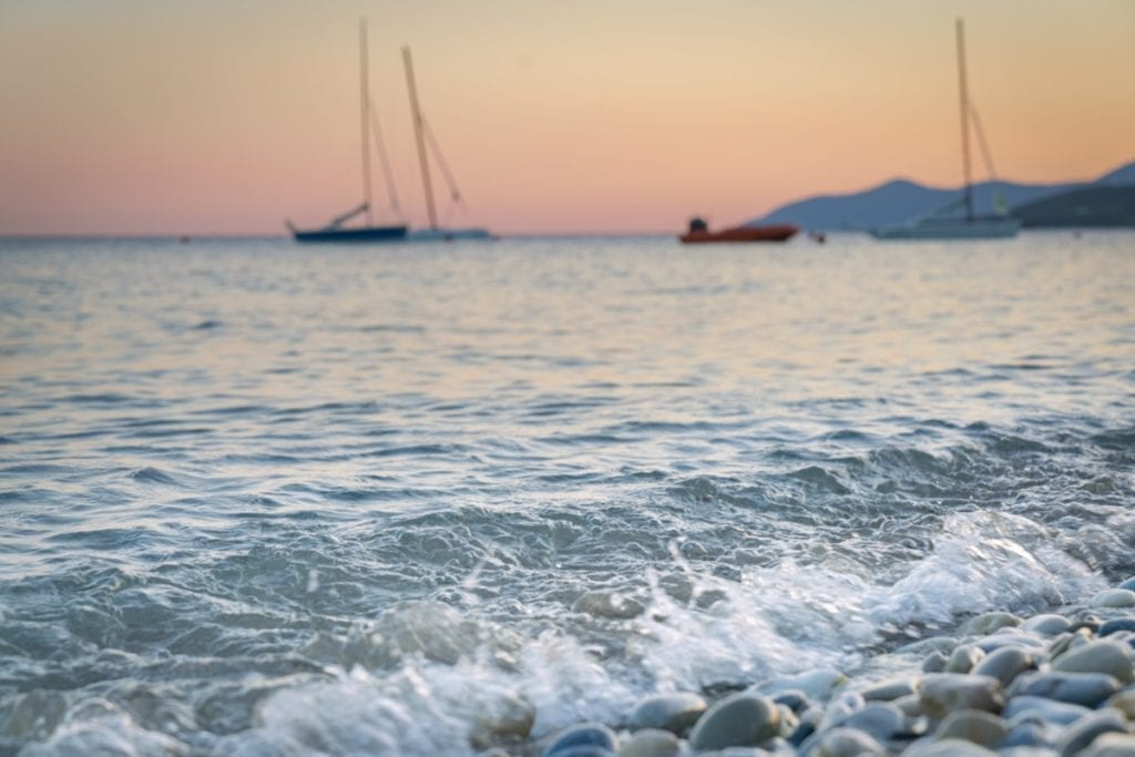 The waves lapping the beach in Samos, Greece as the sun sets on a summer's day