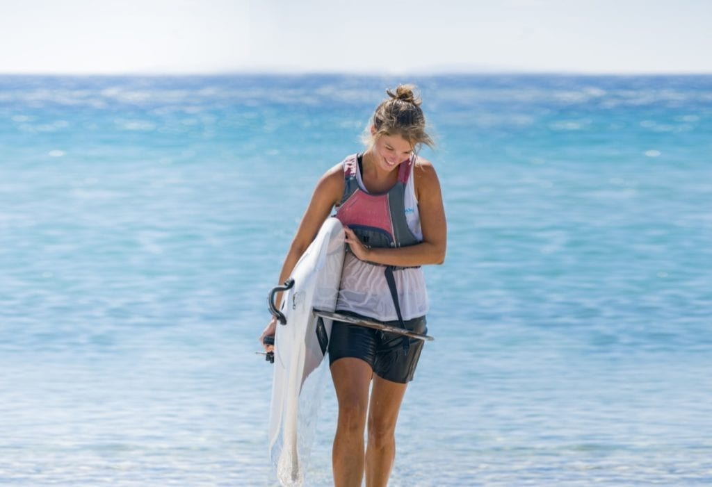 A woman smiling with a windsurf on the beach in Samos, Greece