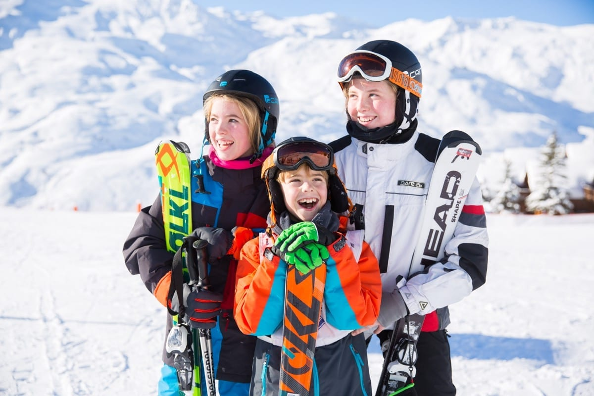 Three siblings with big smiles standing in the snow with their skis on their Christian holiday