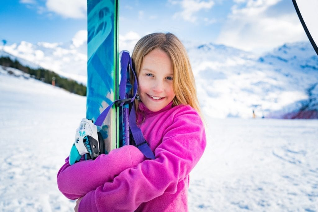 A young girl holding her skis and smiling while on holiday