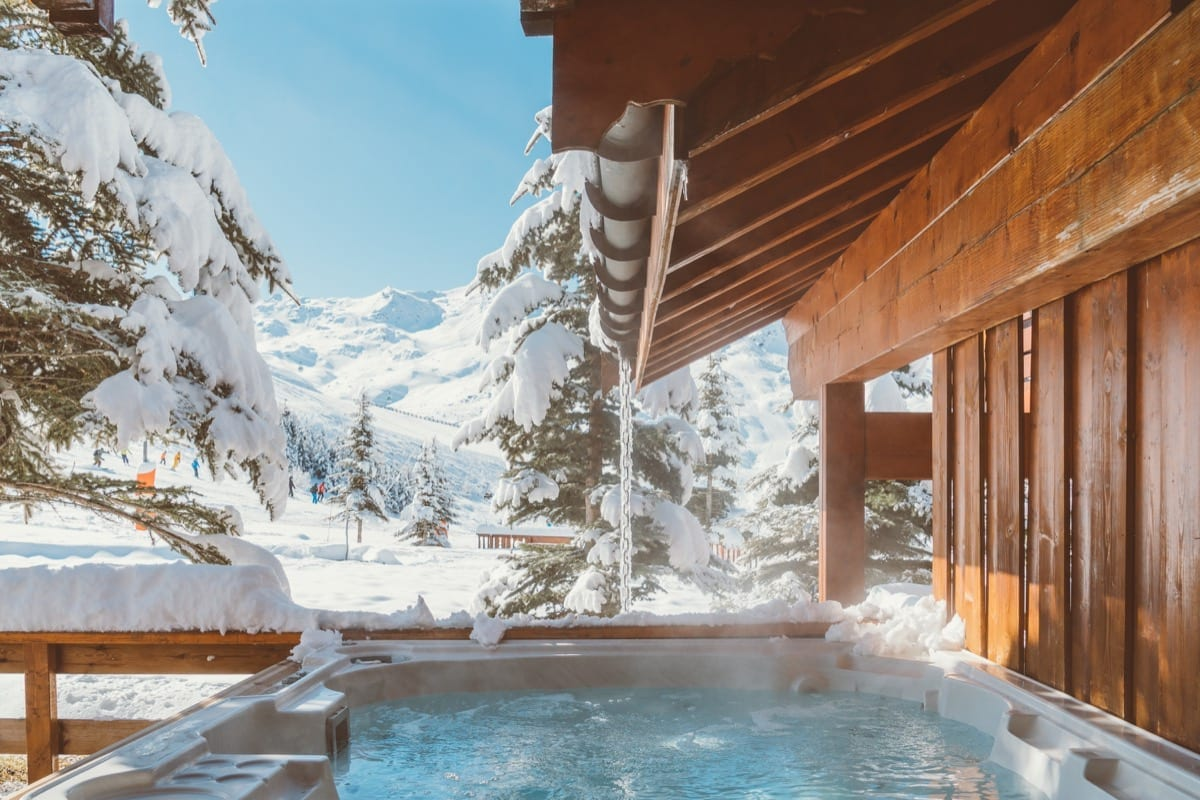 An outdoor hot tub looking over a snowy piste in Reberty village, France