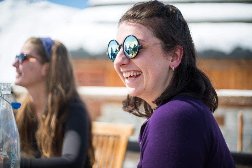 A woman wearing sunglasses and smiling as she has lunch on holiday in the Three Valleys ski resort