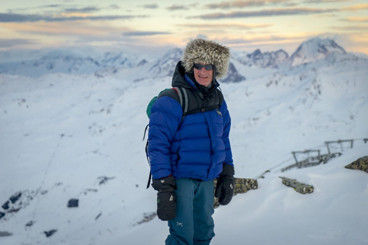 A man dressed for a ski holiday in the snow looking out over the mountains