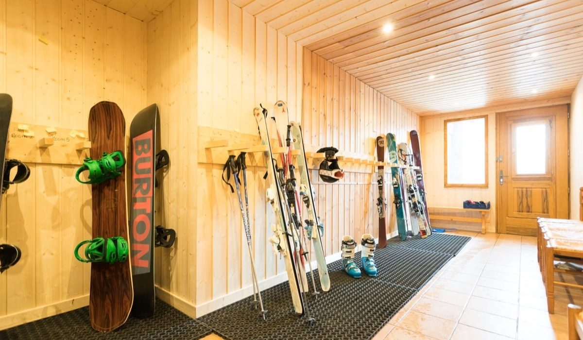 The boot room of Chalet des Neiges, filled with skis and ski boots ready for a day on the slopes