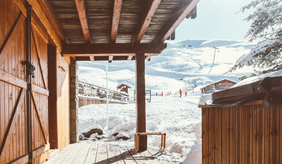 Looking out from the Richmond holidays ski chalet terrace onto the snowy piste with skiers