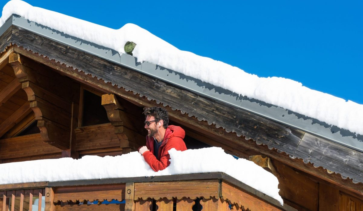 The balcony of the Richmond Holidays chalet with a man smiling in the snow