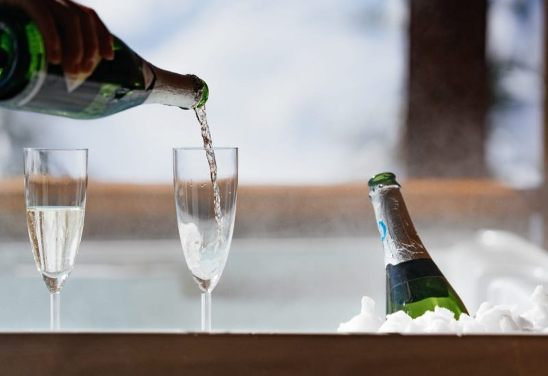 Champagne being poured into glasses by the hot tub of Chalet des Neiges, France