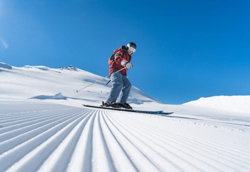 A man skiing on the freshly groomed piste with blue skies and snow
