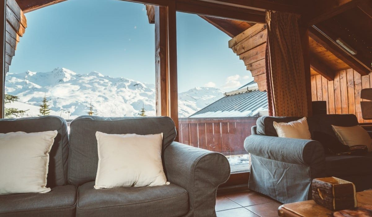 Sofas in the chalet with views of the snow covered mountain in winter
