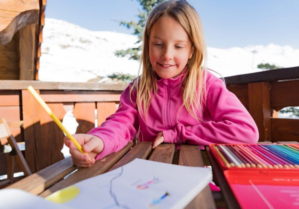 A young girl drawing a picture on the balcony while on a ski holiday